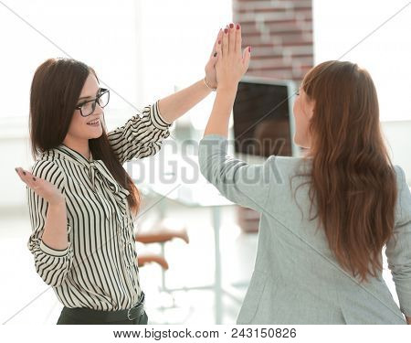 two young co-workers giving each other a high five