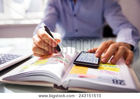 Businessperson Using Mobile Phone While Writing Schedule In Diary