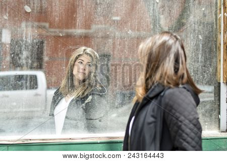 Woman Looking At Her Reflection In A Dirty Window