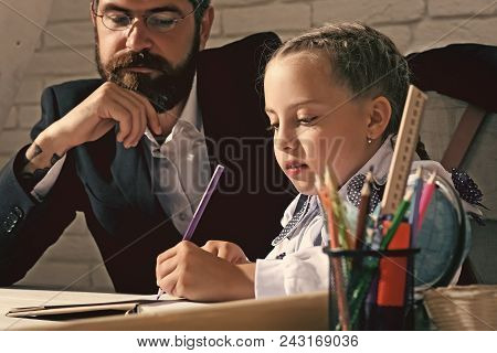 Back To School. Kid And Man Sit By Desk With School Supplies. Schoolgirl And Her Dad With Serious Fa