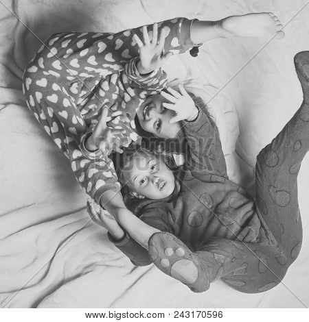 Child Childhood Children Happiness Concept. Children In Pajamas Have Fun In Bed, Top View. Happy Chi