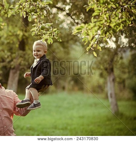 Child Childhood Children Happiness Concept. Trust, Love, Family. Small Boy Sit On Male Hand In Apple