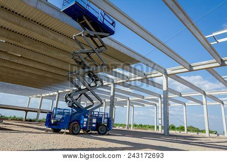Scissor Lift Platform With Stretched Hydraulic System At Maximum Height Range Under Building Skeleto