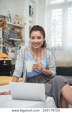 Portrait Of Beautiful Young Asian Woman Enjoying Big Cup Of Coffee And Working On Laptop