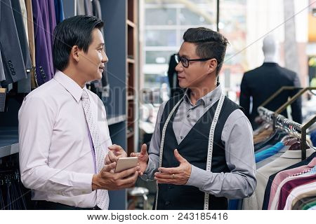 Male Clothing Shop Assistant And Client Discussing