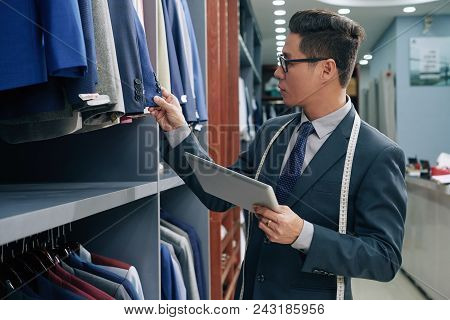 Male Clothing Shop Owner With Tablet Computer Checking Assortment