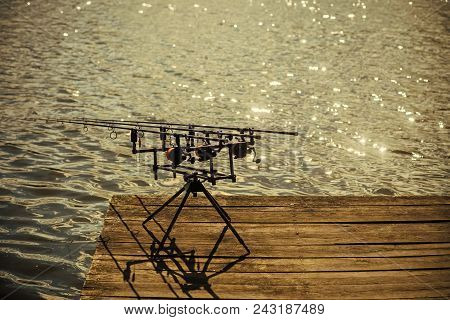 Spin Fishing, Angling, Catching Fish. Spinning Tackles On Pod On Wooden Pier. Fishing, Adventure, Sp