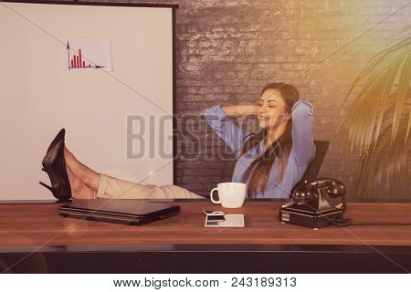 Satisfied Businesswoman, Sitting In The Office And Dreaming About The Future Of Company