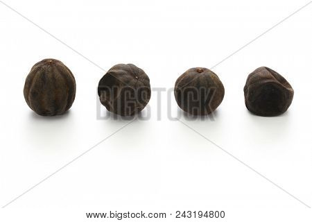 dried persian black lime, limu amani isolated on white background