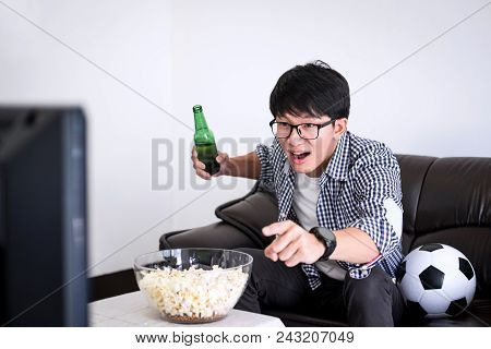 Young Asian Man Fanclub Watching Soccer Match On Tv And Cheering Football Team, Celebrating With Bee