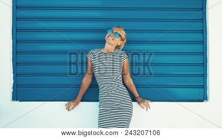 Happy Young Stylish Mediterranean Woman Posing At Blue Roller Shutter High Fashion, Outdoors