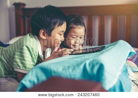 Asian Children Playing Game On Digital Tablet Together. Chinese Boy And His Sister Smiling And Lying