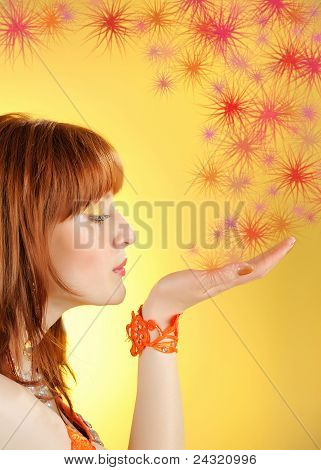 Young Beautiful Woman Blowing Golden Stardust From Her Hand