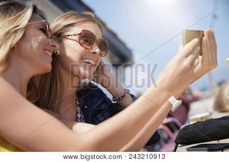 Trendy girls taking selfie pictures with smartphone