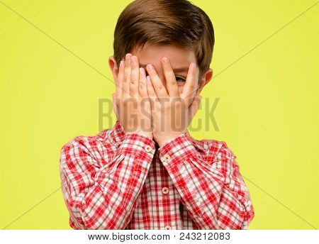 Handsome toddler child with green eyes smiling having shy look peeking through fingers, covering face with hands looking confusedly broadly over yellow background