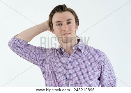 Pensive Handsome Young Guy With Stubble Scratching Back Of Head. Puzzled Shy Man In Casual Shirt For