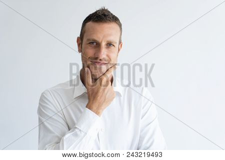 Portrait Of Mid Adult Businessman With Interested Expression Touching His Chin. Caucasian Manager We