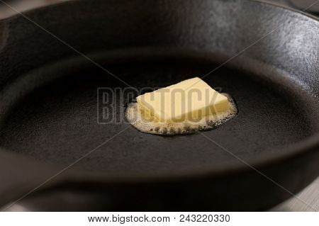 A Butter Pat Melting On A Black Cast Iron Frying Pan.