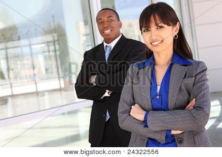 A pretty asian woman with handsome african american business man coworker in background