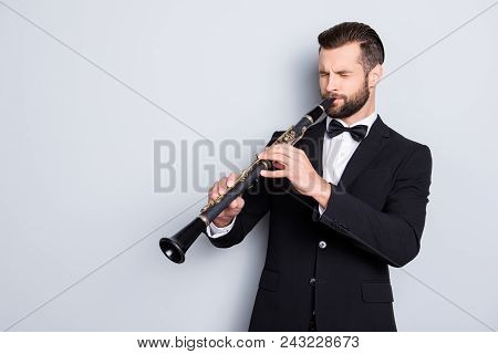Portrait with copy space, empty place of stylish talented man with hairstyle in black tux with bow playing from heart on bassoon with closed eyes, isolated on grey background poster