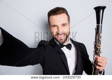 Self portrait of creative cheerful man in tux shooting selfie on front camera with arm, having showing bassoon, isolated on grey background, having rest relax leisure fun video-call poster