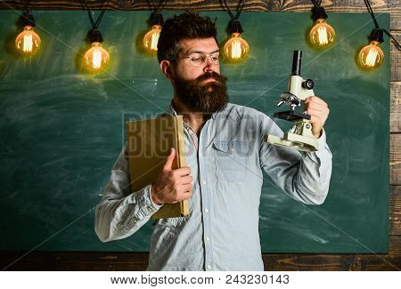 Hipster Teacher With Microscope, Big Blackboard. Man With Beard And Mustache On Strict Face In Class