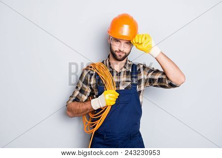 Portrait Of Virile Harsh Electrician With Bristle In Overall, Shirt, Having Rolled Cable On Shoulder