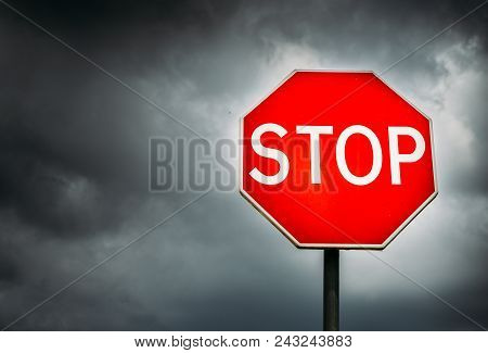 Conceptual Stop Sign With Stormy Background And Copy Space. Metaphor For Warning, Caution And Danger
