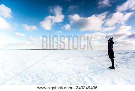 One Girl Standing At The Edge Of Frozen Sea And Looking Away Contemplating The Frozen Waves In Winte