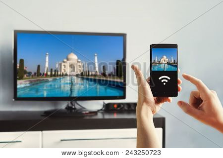 Male Hand Holding A Smartphone Against View Of Living Room With A Large Screen Tv. Use Wi Fi To Tran