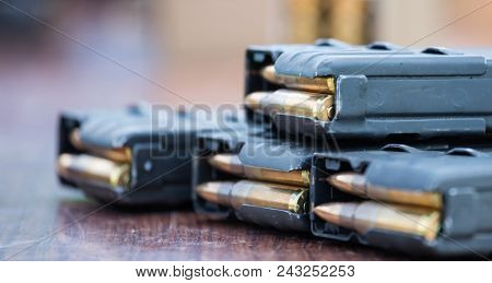Blue magazines with bullets of firearm putted on wooden table. Ammunition for protection of soldiers. Close up view, blurred background.
