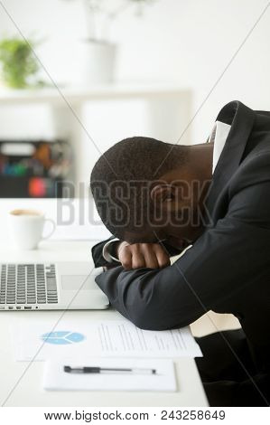 Overworked sleepy exhausted unhappy person having nap at workplace, feeling lazy, unmotivated after too much work done. Depressed black worker hopeless at company bankruptcy news, no motivation poster