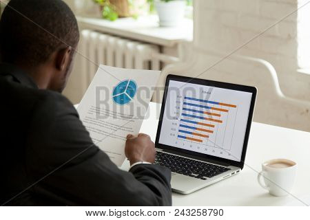 African American Employee Holding Handout With Presented Diagram, Comparing Financial Data With Stat