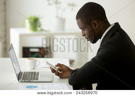 Focused Serious Young African American Person Checking Email On Smartphone, Looking At Phone While W
