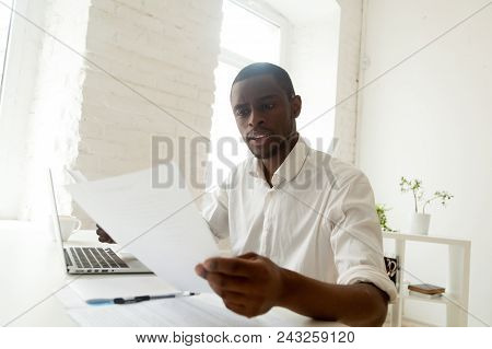 Concentrated African American Manager Reading Letter, Paper Handout, Analyzing Company Statistics, T
