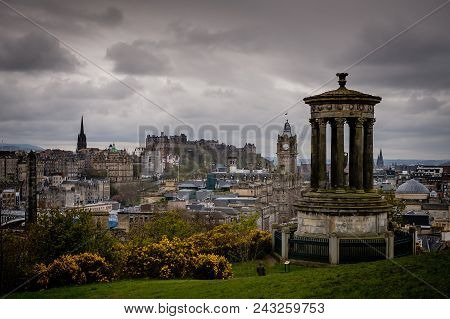 Edinburgh City And Castle, Scotland, Viewed From Calton Hill On A Cloudy Afternoon With The Dugald S