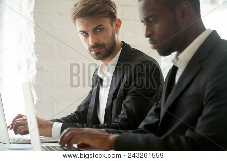 Suspicious cunning male Caucasian worker looking at serious working African American colleague, feeling mad and sneaky distrusting, having doubts, planning. Concept of office relationships, jealousy poster