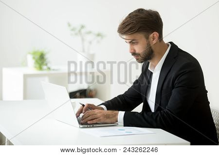 Serious Caucasian Businessman Wearing Formal Wear Working At Laptop Typing, Answering To Business Pa