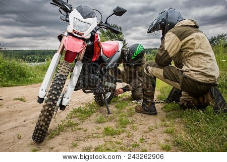 Two Men In Motorcycle Gear Checking Rear Wheel Of Dirtbike. Adjusting Bolt With Socket Wrench On Bik