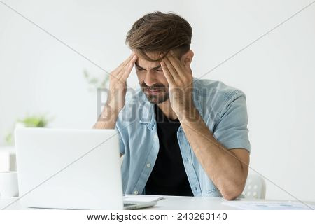 Exhausted Male Worker Massaging Head, Suffering From Severe Headache, Tired After Long Working Hours