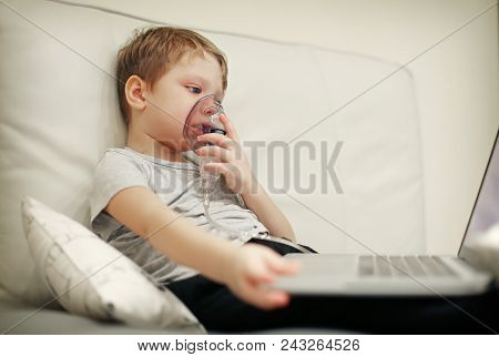 Sick Chid With Pediatric Nebulizer Mask In Front Of Laptop. Little Kid With Asthma Or Bronchitis Has