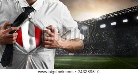 Peru soccer or football supporter showing flag under his business shirt on stadium.