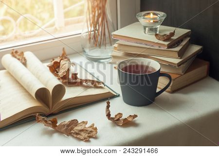 Autumn Still Life. Books, Leaves, Cuo Of Tea And Dry Tiny Flowers In Vase Red Candlestick With A Bur