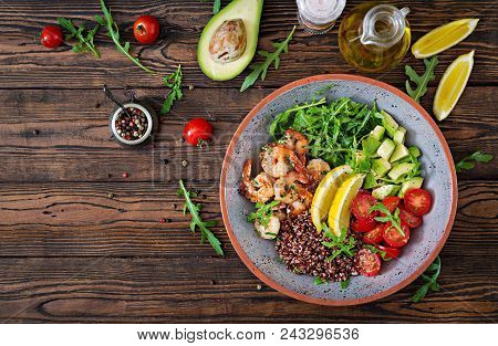 Delicious Healthy Buddha Bowl With Shrimps, Tomato, Avocado, Quinoa, Lemon And Arugula On The Wooden