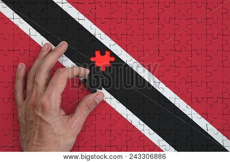 Trinidad And Tobago Flag  Is Depicted On A Puzzle, Which The Man's Hand Completes To Fold