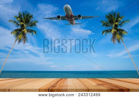 Passenger Airplane And Tropical Palm On A Paradise Island, Empty Wooden Table And Palm Leaves With P