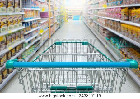 Supermarket Aisle With Empty Blue Shopping Cart With Customer Defocus Background