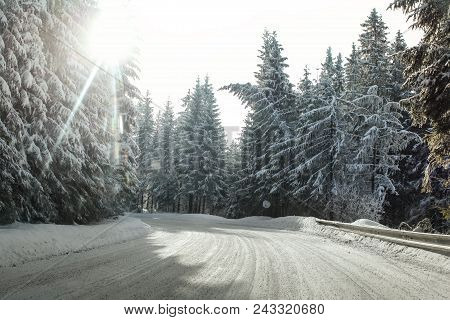 View From A Car Riding Through Snow Covered Winter Road Curve, Lit By Strong Sun Backlight - Dangero