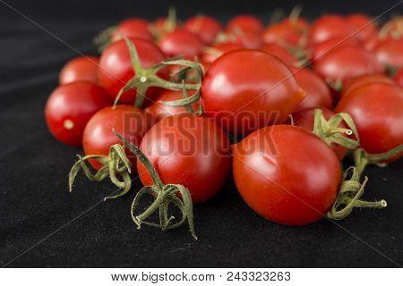 tiny cherry tomatoes, black background,tiny tasty skin tomatoes,
