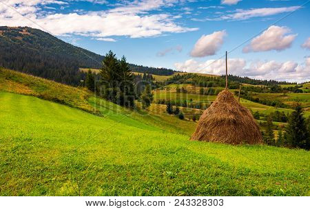 Haystack On A Grassy Meadow In Mountains. Beautiful Landscape Under The Azure Sky With Gorgeous Clou